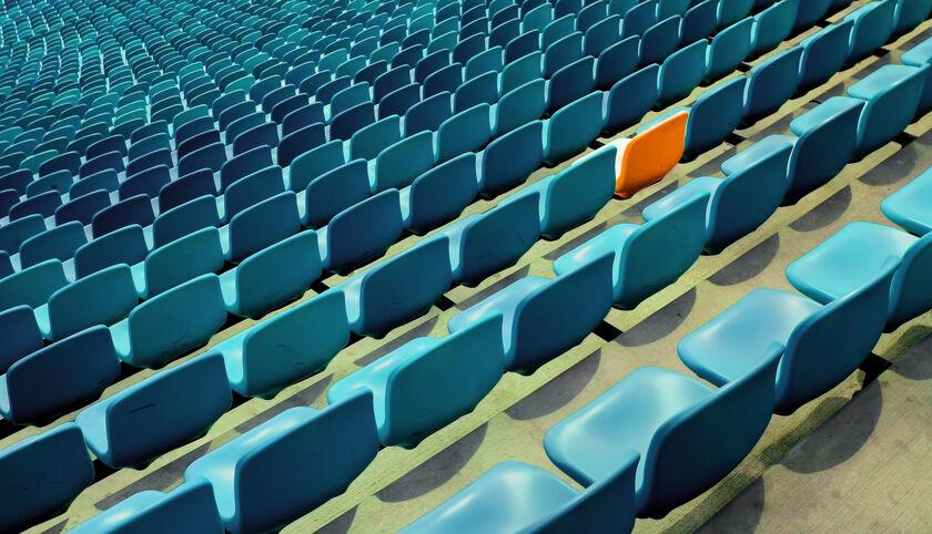 Blaue Sitze im Stadion mit einem Sitz in Orange